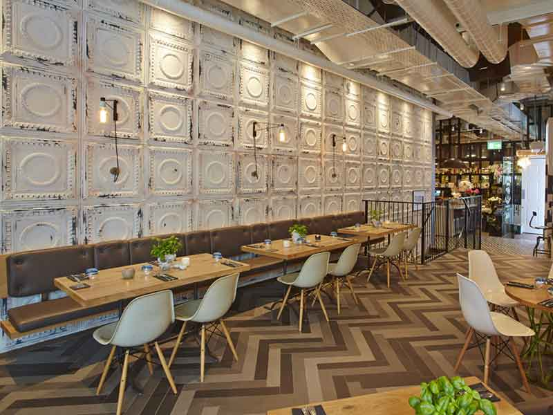 central to the industrial look is a long feature wall created from embossed metal tiles finished in a heavily distressed antique white finish